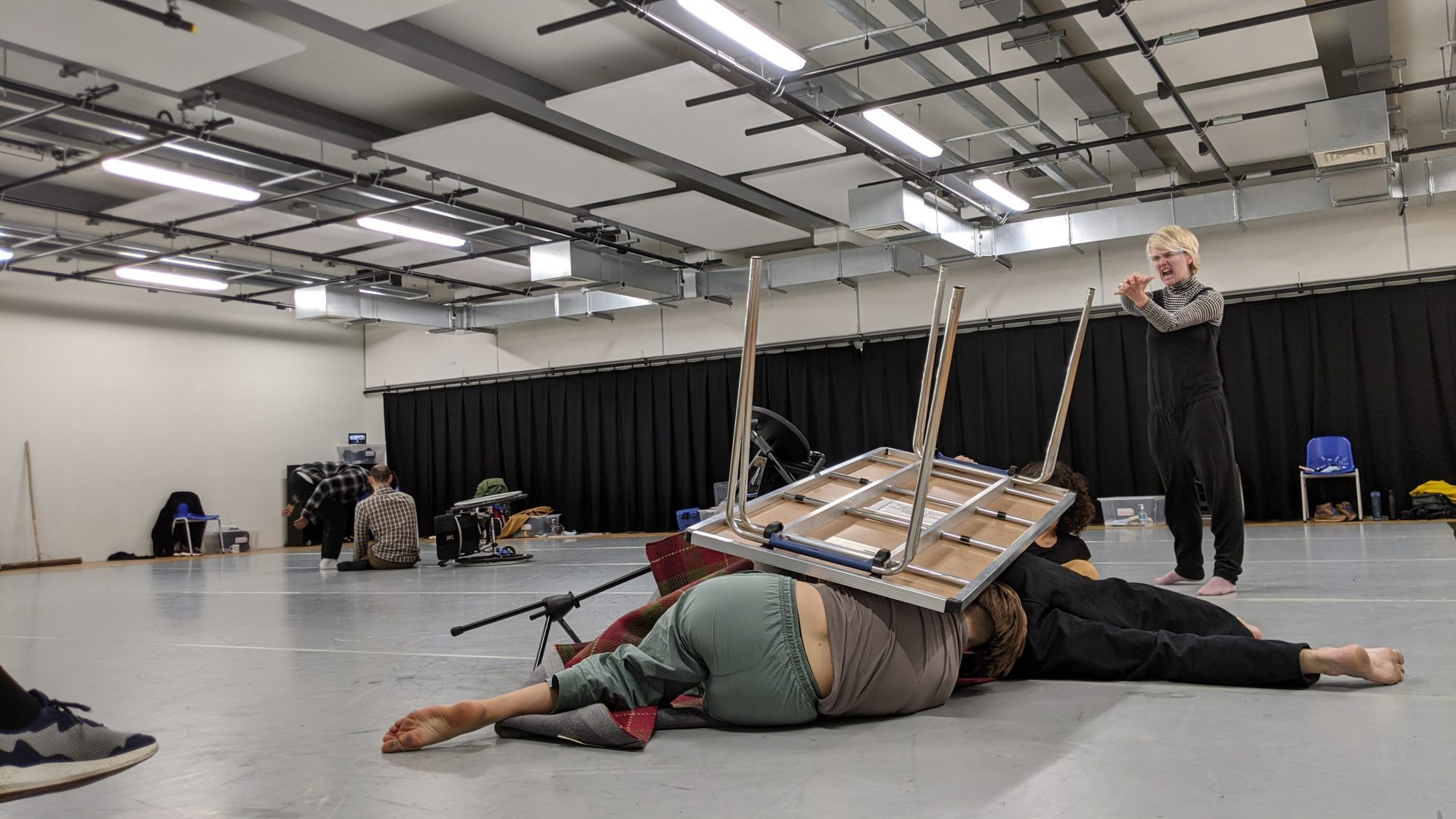 Dancers Under a Table Last Shelter Rehearsal